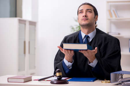 Young male judge working in courthouse