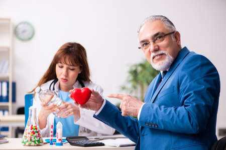 Old businessman visiting young female doctor