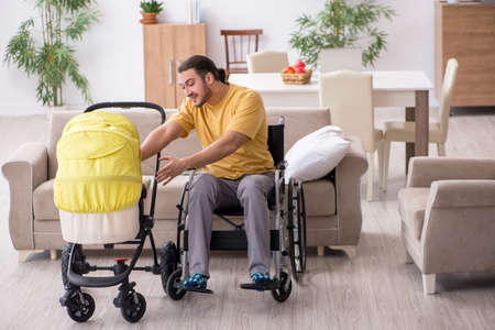 Young man contractor in wheel-chair looking after newborn