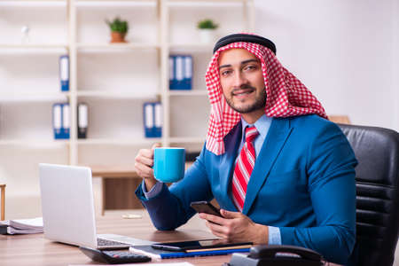 Young male arab employee working in office