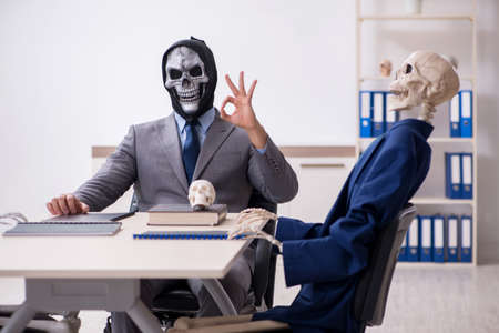 Funny business meeting with devil and skeletons Foto de archivo