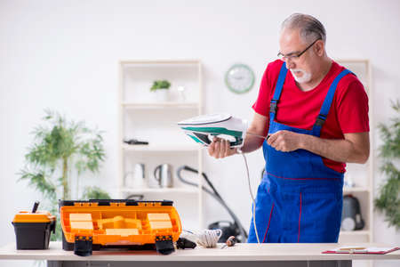 Old male contractor repairing iron indoors