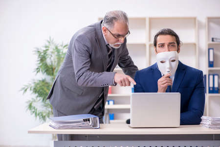 Old boss and young male employee wearing masks