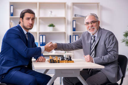 Two businessmen playing chess in the office Foto de archivo