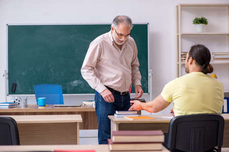 Old teacher and young male student in the classroom Banque d'images