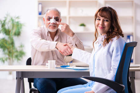Old man visiting young female doctor for plastic surgery Banque d'images