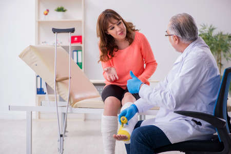 Young leg injured woman visiting old doctor traumatologist