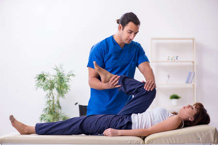 Injured woman visiting young male doctor osteopath