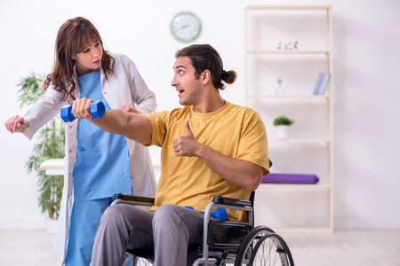Young male patient in wheel-chair doing physical exercises Banque d'images