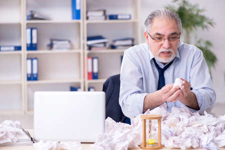 Old businessman rejecting new ideas with lots of papers Imagens