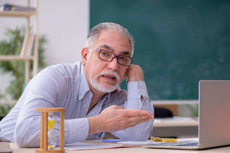 Old male teacher in the classroom Imagens