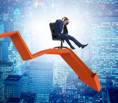 Businessman sliding down on chair in economic crisis concept