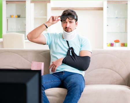 Man with neck and arm injury watching tv Banque d'images