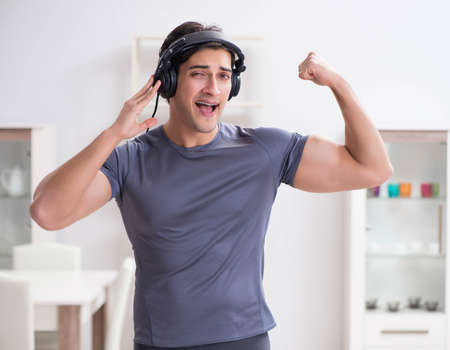 Man doing sports at home and listening to music