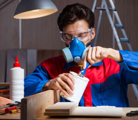 Young man gluing wood pieces together in DIY concept Imagens