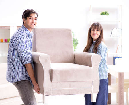 Man moving armchair in the living room Imagens