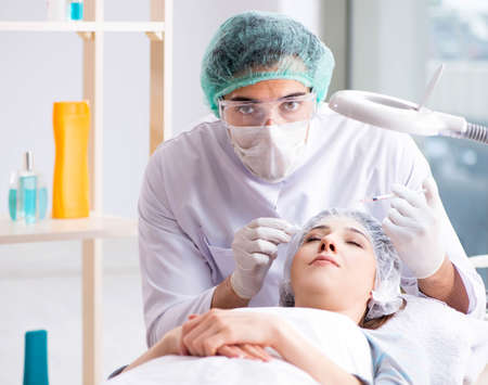 Woman visiting doctor for plastic surgery Imagens