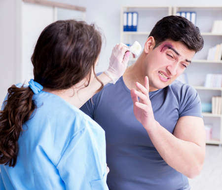 Young man visiting female traumatologist with black eye Banque d'images