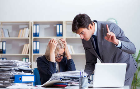 Angry irate boss yelling and shouting at his secretary employee Stock fotó