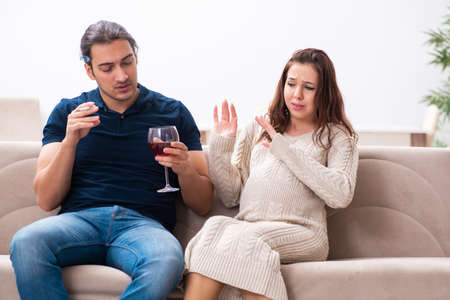 Man and pregnant woman in harmful habits concept Stock Photo