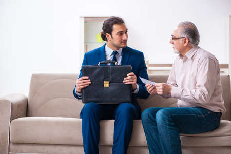 Young male lawyer visiting old man in testament concept Фото со стока