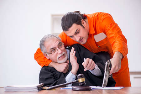 Old male judge meeting with young captive in courthouse Foto de archivo