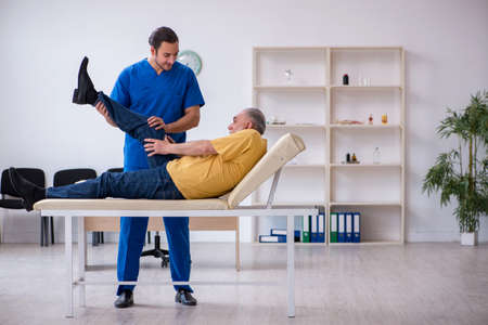 Old injured man visiting young male doctor chiropractor Stock Photo