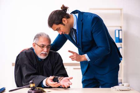 Police inspector arresting old judge in court