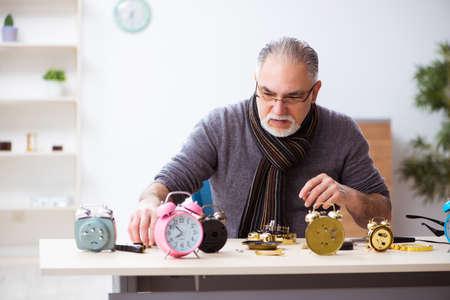 Old male watchmaker working in the workshop Standard-Bild