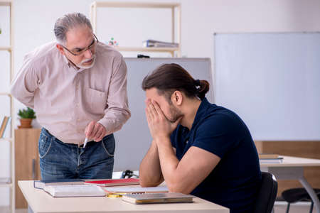 Old teacher and young male student in the classroom