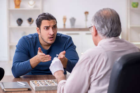 Young man visiting old male jeweler