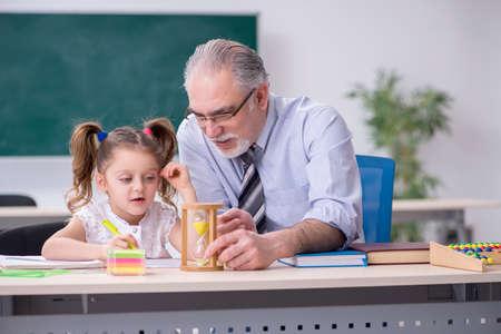 Old teacher and schoolgirl in the school