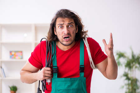 Funny young male electrician working indoors