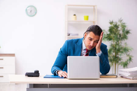 Sick male employee suffering at workplace from coronavirus Stockfoto