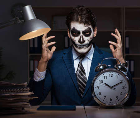 Businessman with scary face mask working late in office Banque d'images