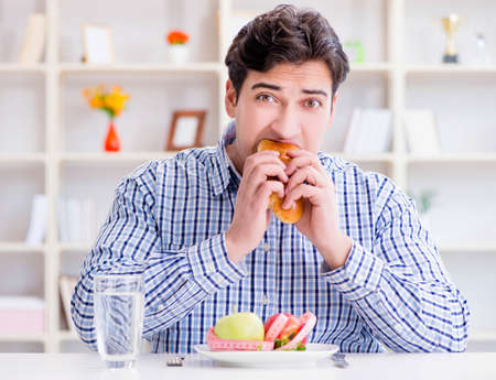 Man having dilemma between healthy food and bread in dieting con Stock Photo