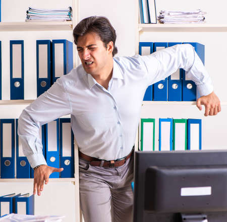Young male employee working in the office Banque d'images