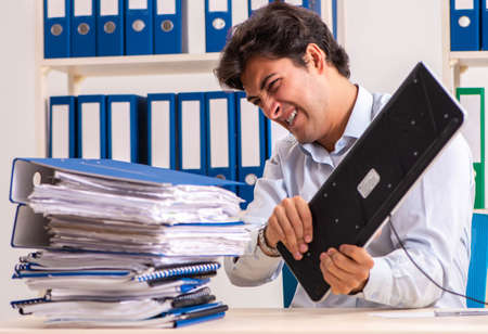 Overloaded busy employee with too much work and paperwork Stock Photo