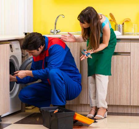 Contractor repairing washing machine at home