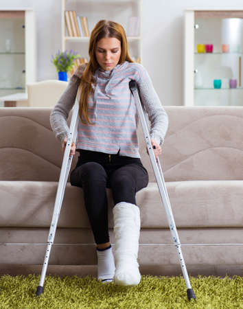 Young woman with broken leg at home Banque d'images