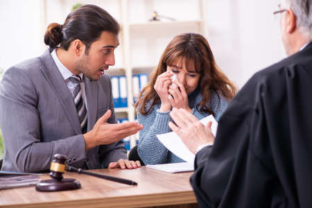 Young woman in courthouse with judge and lawyer