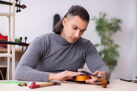 Young male repairman repairing violin