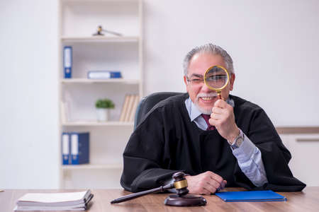 Old male judge working in the courthouse