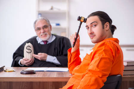 Old male judge meeting with young captive in courthouse Banque d'images