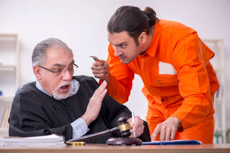 Old male judge meeting with young captive in courthouse