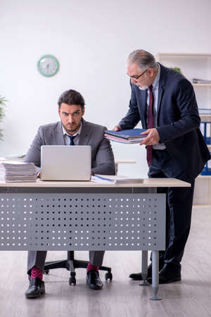 Old boss and his young assistant working in the office Imagens