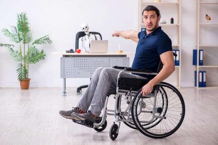 Young man in wheel-chair visiting dead doctor Foto de archivo