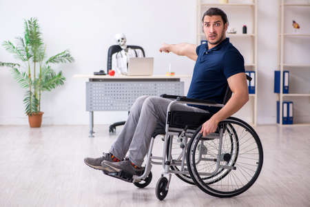 Young man in wheel-chair visiting dead doctor Imagens