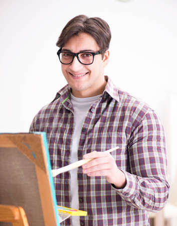 The young male artist drawing pictures in bright studio