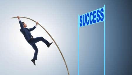 Businessman pole vaulting over towards his success career Standard-Bild